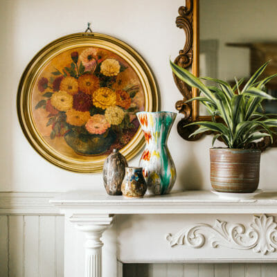 Decorative white mantle with gilded mirror, pottery, plants and a circular floral painting at Mazet in Three Oaks, Michigan.