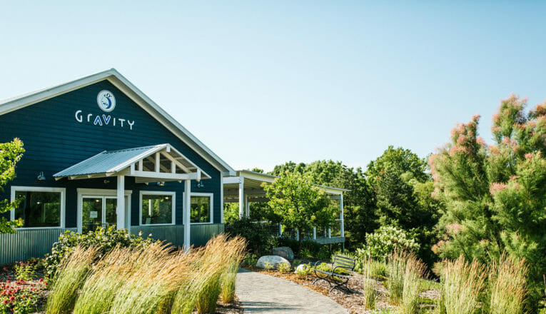 View of Gravity Vineyards and Winery's tasting room with with lush green landscaping in Baroda, Michigan.