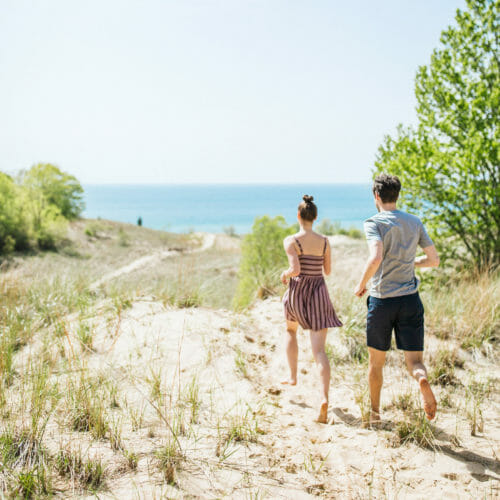 Couple frolicking on the sand dunes with a view of Lake Michigan at Warren Dunes State Park in Sawyer, Michigan.