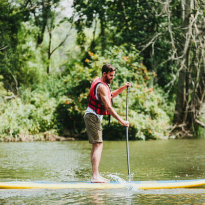 A bearded young man in an orange life vest and shorts paddling on a stand-up board on Galien River Marsh Train in New Buffalo, Michigan.