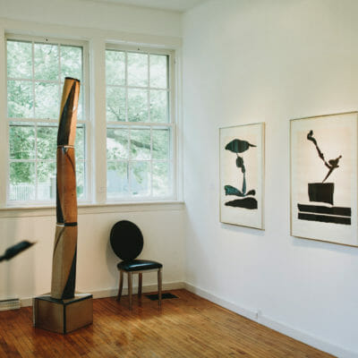Graphic black and white prints and a tall organic wooden sculpture at Judith Racht Gallery in Harbert, Michigan.