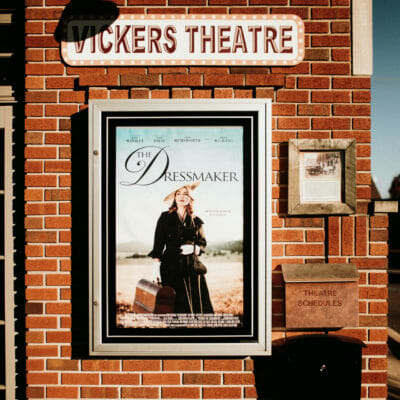 A movie poster on the brick exterior of Vickers Theatre in Three Oaks, Michigan.