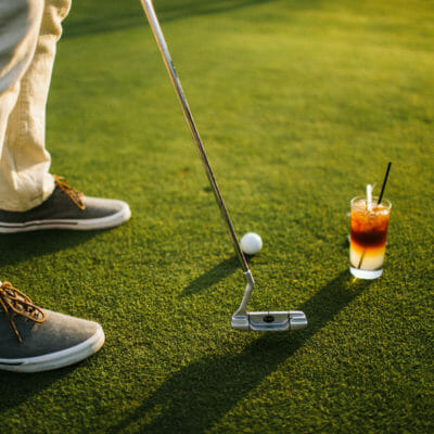 detailed image of tennis shoes a putter and golf ball and a cocktail